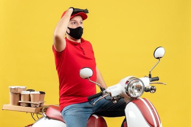 Widok z góry młodego dorosłego noszącego czerwoną bluzkę i rękawiczki w masce medycznej dostarczającego zamówienie siedzącego na skuterze skupionym na czymś na żółtym tle
