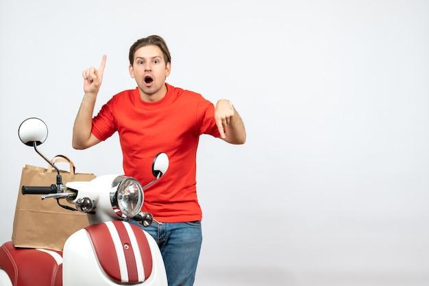 Widok z góry młodego faceta dostawy z kciukami w górę iw dół w czerwonym mundurze stojącym w pobliżu skutera na białej ścianie