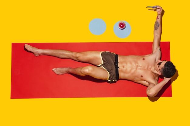 Widok z góry młodego kaukaskiego modelu męskiego odpoczywającego na plaży