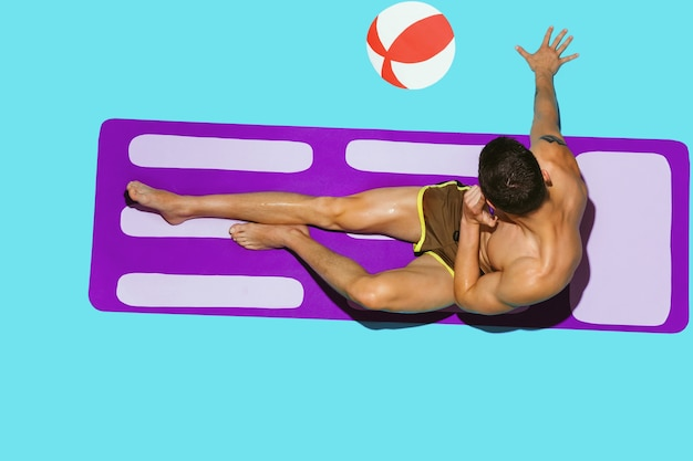 Widok z góry młodego modelu kaukaski mężczyzna odpoczywa na plaży na fioletowej macie