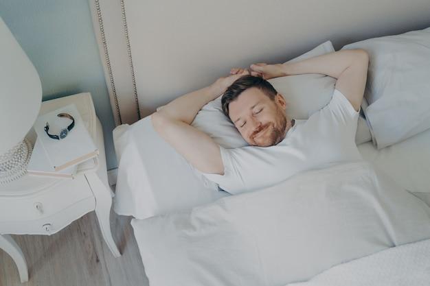 Widok z góry młodego szczęśliwego zrelaksowanego kaukaskiego mężczyzny z atrakcyjnym uśmiechem śpiącego w wygodnym łóżku z białą pościelą. zdrowa opieka, dobry sen i odpoczynek w nocy