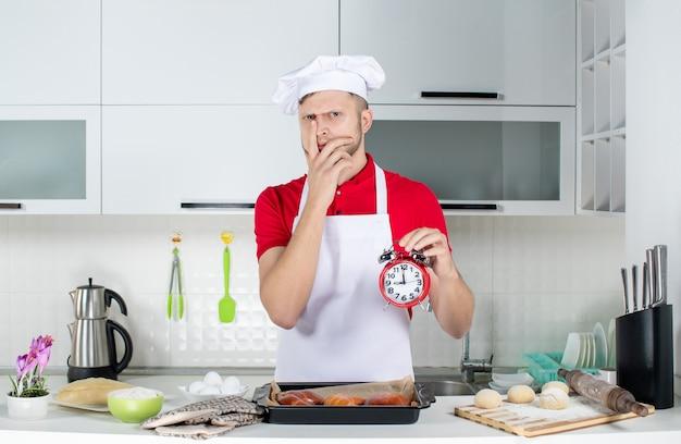 Widok z góry młodego szefa kuchni mężczyzny trzymającego zegar i czującego się zdezorientowanym w białej kuchni