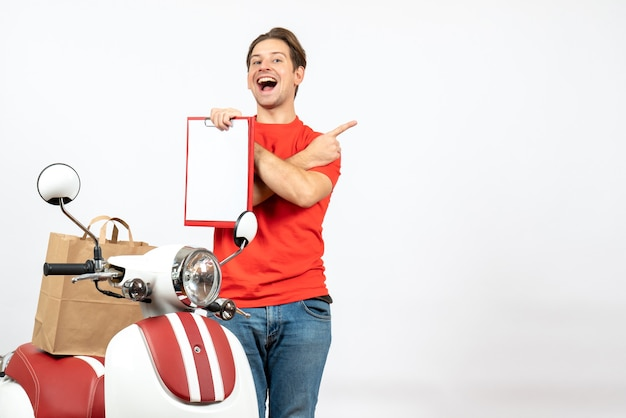 Widok z góry młodego uśmiechniętego faceta dostawy w czerwonym mundurze stojącego w pobliżu skutera pokazującego dokument i wskazującego z powrotem na białej ścianie
