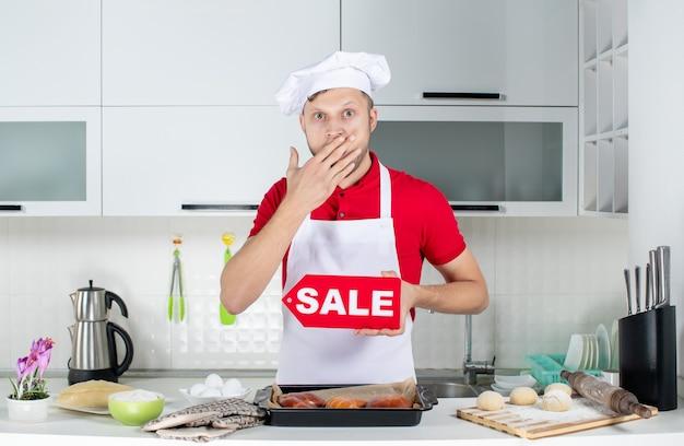 Widok z góry młodego zdziwionego szefa kuchni pokazującego znak sprzedaży w białej kuchni