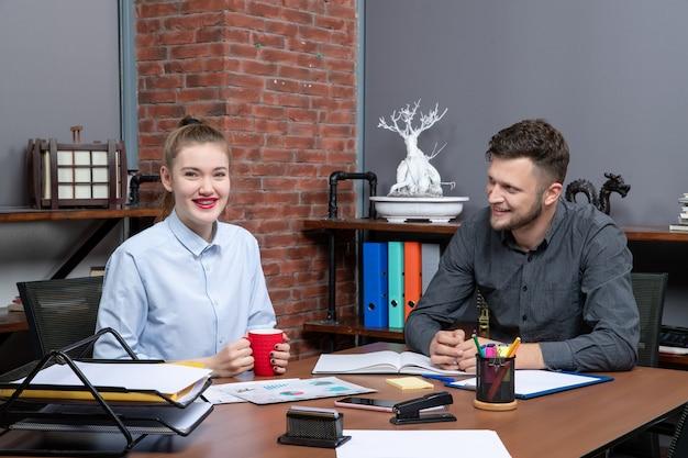 Widok z góry młodej asystentki biurowej i jej męskiego współpracownika siedzących przy stole, omawiających jakiś problem w biurze