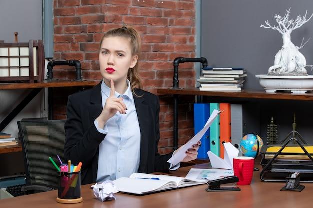 Widok z góry młodej damy siedzącej przy stole i trzymającej dokument skierowany w górę w biurze