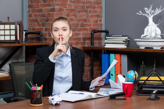 Widok z góry młodej damy siedzącej przy stole i trzymającej dokument wykonujący gest ciszy w biurze