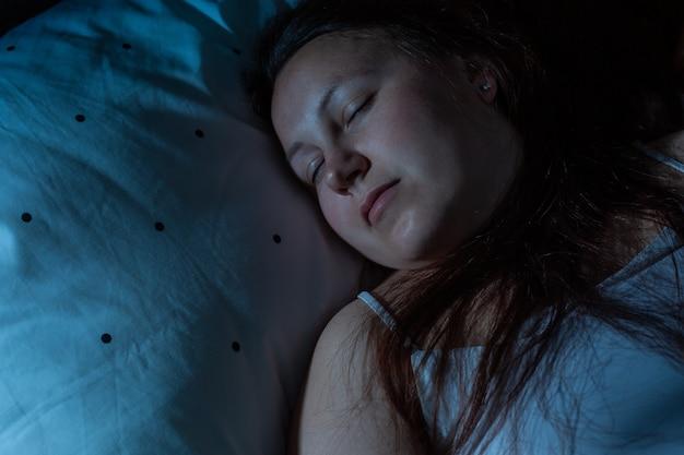 Widok z góry młodej kobiety przytulnie śpiącej na łóżku w nocy, niebieskie kolory nocne