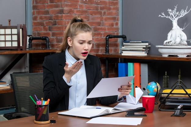 Widok z góry młodej kobiety siedzącej przy stole i trzymającej dokument czytający coś z wyrazem twarzy w biurze