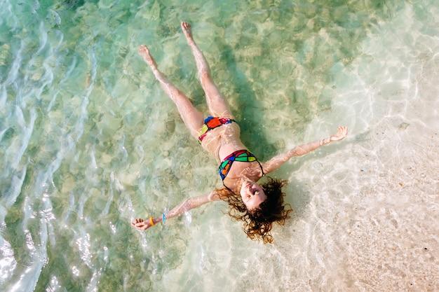Widok z góry młodej kobiety w jasnym bikini pływa w przejrzystym, błękitnym morzu. widok z lotu ptaka szczupła kobieta kłama i unosi się na wodzie andaman morze. phuket, tajlandia.