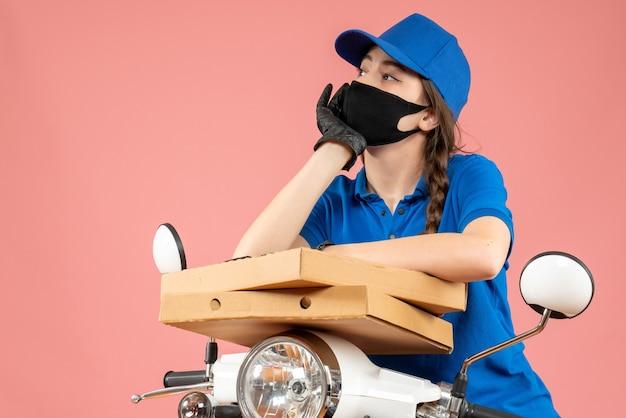 Widok z góry młodej myślącej kurierki w masce medycznej i rękawiczkach, trzymającej pudełka na pastelowej brzoskwini