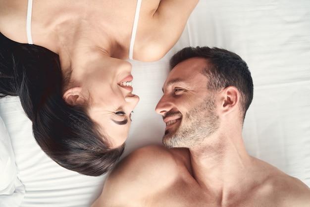 Widok z góry młodej pary leżącej twarzą w twarz na prześcieradle w łóżku