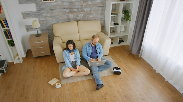 Widok z góry młodej pary przeglądania na laptopie i smartfonie, siedząc na dywanie.