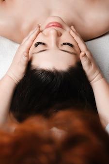 Widok z góry młodej pięknej kobiety rasy kaukaskiej wykonującej masaż twarzy w salonie spa przez kosmetologa przed zabiegami na twarz.