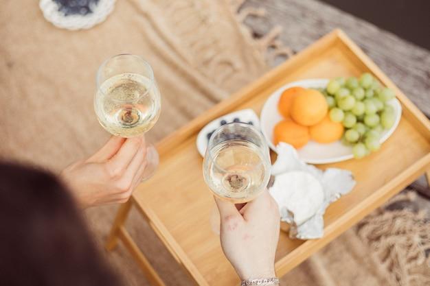 Widok z góry młodej szczęśliwej pary nie do poznania na pikniku w pobliżu rzeki lub jeziora, kobieta i mężczyzna razem piją wino na zewnątrz, ludzie bawią się na wakacjach, kochają emocje