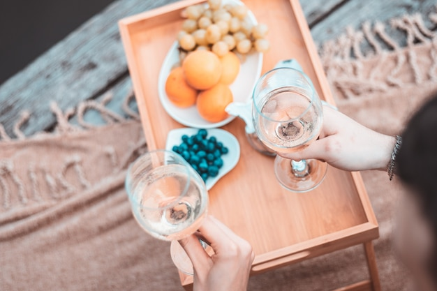 Widok z góry młodej szczęśliwej pary nie do poznania na romantycznym pikniku w pobliżu rzeki lub jeziora, kobieta i mężczyzna razem piją wino na zewnątrz, ludzie bawią się na wakacjach, kochają emocje