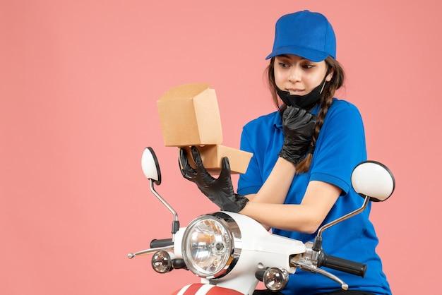 Widok z góry młodej uśmiechniętej kurierki ściągającej jej maseczkę medyczną i rękawiczki otwierające pudełko na pastelowej brzoskwini