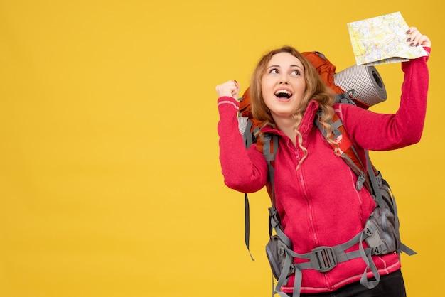 Widok z góry młodej uśmiechniętej pozytywnej dziewczyny podróżującej w masce medycznej, trzymając i pokazując mapę