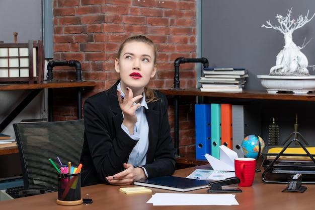 Widok z góry młodej zamyślonej pracowniczki biurowej siedzącej przy biurku i pozującej do kamery