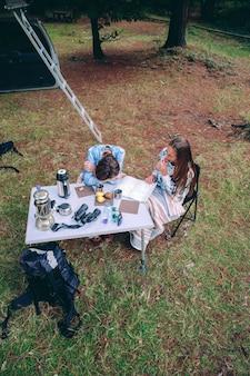 Widok z góry młodych kobiet jedzących śniadanie na kempingu nad przyrodą?