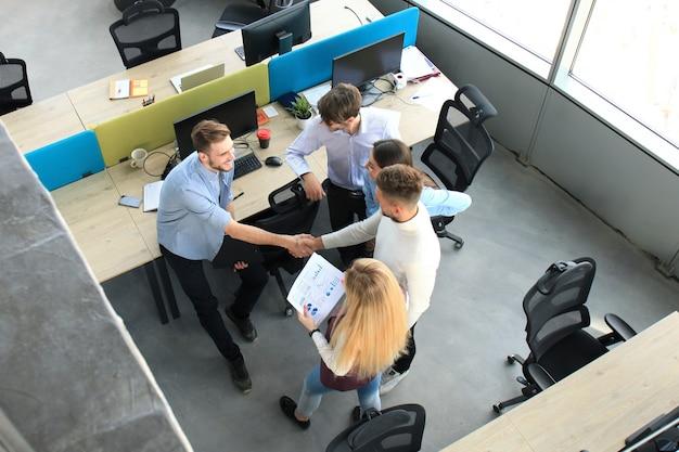 Widok z góry młodych partnerów biznesowych, ściskając ręce nad interesem w biurze. skoncentruj się na drżenie ręki.