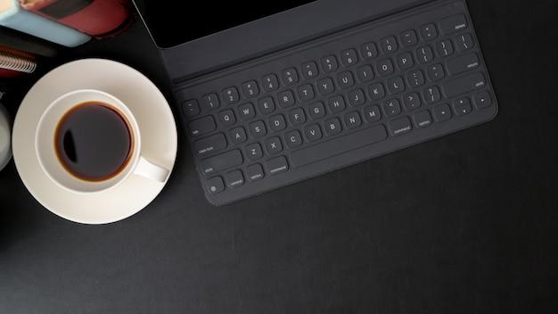 Widok z góry modnego obszaru roboczego z cyfrowym tabletem, filiżanką kawy, książkami i miejsca kopiowania