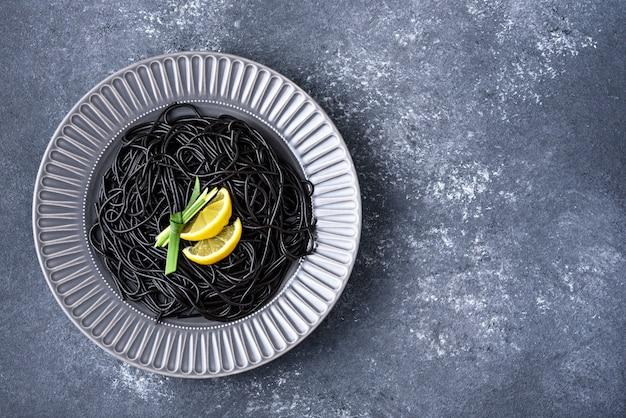 Widok z góry modny czarny makaron z tuszem mątwy z plasterkami cytryny i liściem w szarym talerzu na szarym tle z miejscem na kopię