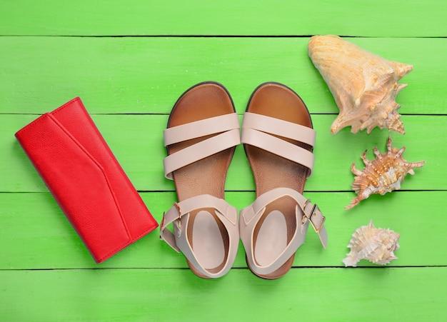 Widok z góry modnych damskich sandałów, czerwonej torebki i muszelek