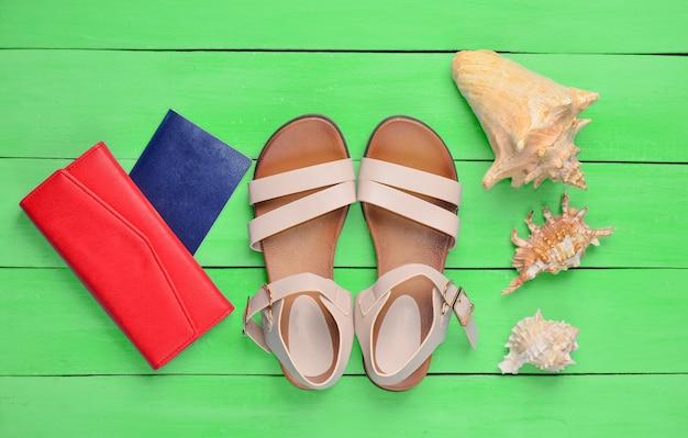 Widok z góry modnych damskich sandałów, paszportu, czerwonej torebki i muszelek