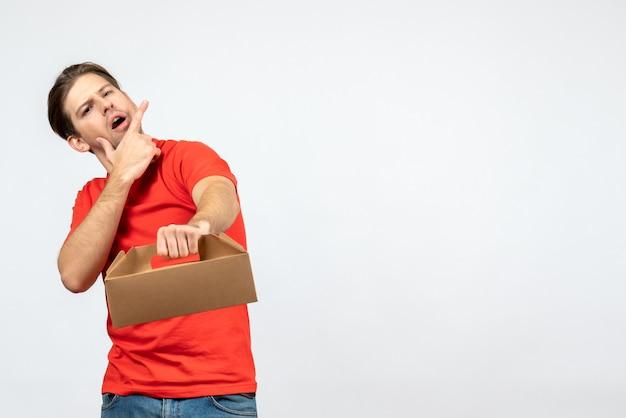 Widok z góry myślenia młodego człowieka w czerwonej bluzce, trzymając zamówienia na białej ścianie