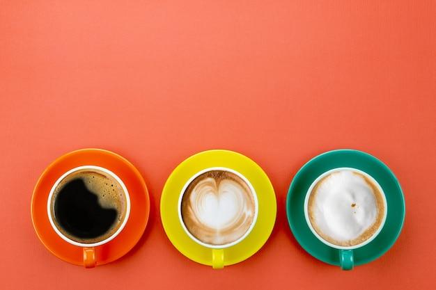 Widok z góry na 3 style kawy z czarną kawą latte i cappuccino w pomarańczowo-żółtej i zielonej filiżance