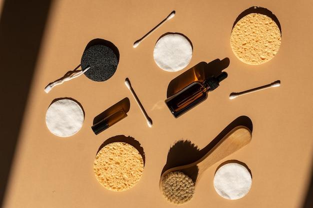 Widok z góry na akcesoria do suchego masażu i kosmetyki. ekologiczna koncepcja kosmetyków zero waste. naturalna drewniana szczoteczka do twarzy, płatki kosmetyczne, patyczki do uszu i kosmetyczne olejki eteryczne w butelkach z ciemnego szkła.