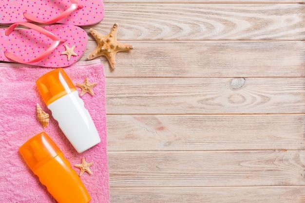 Widok z góry na akcesoria płaskie świeckich plaży. krem do opalania butelka z muszelek, rozgwiazdy, ręcznik i klapki na tle drewnianej deski z miejsca kopiowania.
