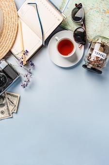 Widok z góry na akcesoria podróżne, planowanie podróży aparat, notatnik, filiżanka herbaty. słoik monet