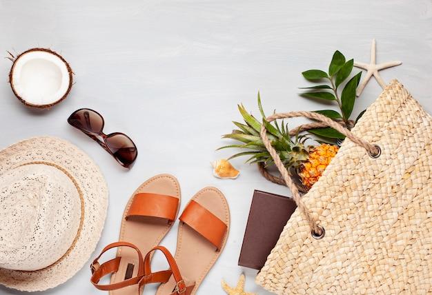 Widok z góry na akcesoria tropikalnej plaży z letnią torbą ze słomy i klapkami