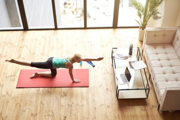 Widok z góry na aktywną dojrzałą kobietę w odzieży sportowej po treningu na macie w domu przed laptopem