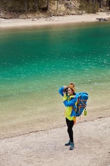 Widok z góry na aktywną kobietę stojącą nad brzegiem turkusowego górskiego jeziora, strzela coś do aparatu, nosi dużą torbę