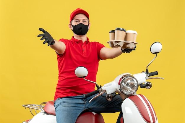 Widok z góry na ambitnego uśmiechniętego dostawcę w rękawiczkach mundurowych i kapeluszowych w masce medycznej, siedzącego na skuterze, pokazującego zamówienia mówiące o czymś