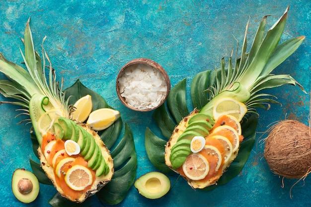 Widok z góry na ananasowe łódki z wędzonym łososiem i plastry awokado z jajkami cytrynowymi i przepiórczymi