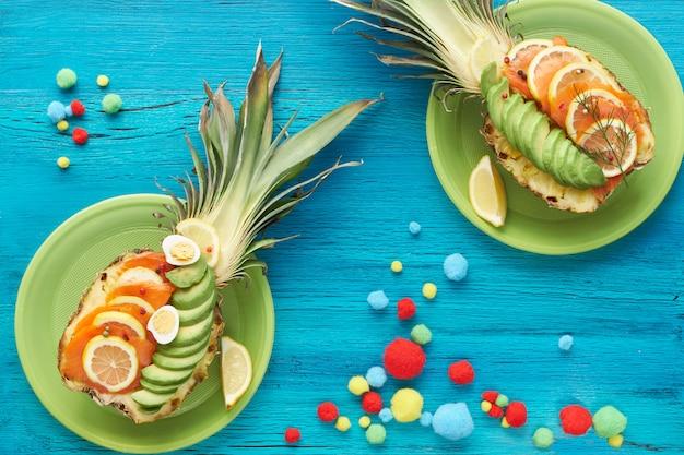 Widok z góry na ananasowe łódki z wędzonym łososiem i plastry awokado z jajkami cytryny i przepiórki