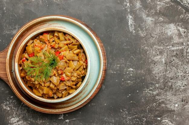Widok z góry na apetyczne danie fasolka szparagowa z pomidorami na drewnianej tacy na desce do krojenia na ciemnym stole