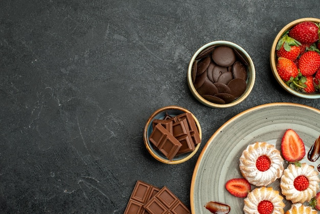 Widok z góry na apetyczne słodycze ciasteczka z truskawkami i miski z truskawkami i czekoladą po prawej stronie ciemnego stołu