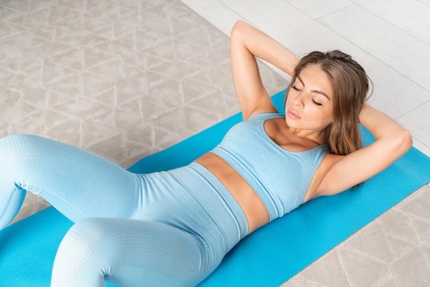 Widok z góry na atrakcyjną młodą, sprawną kobietę, która ćwiczy mięśnie brzucha w domu w przytulnym wnętrzu