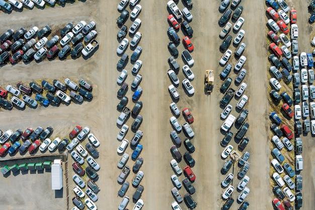 Widok z góry na aukcję samochodową z wieloma używanymi samochodami zaparkowanymi na parkingu.