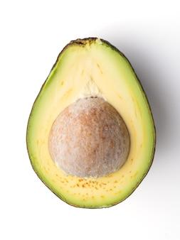 Widok z góry na awokado przekrojone na pół na białym tle, miąższ awokado jest kremowy i miękki o maślanym smaku. awokado zawiera składniki odżywcze, witaminy i dobre tłuszcze.