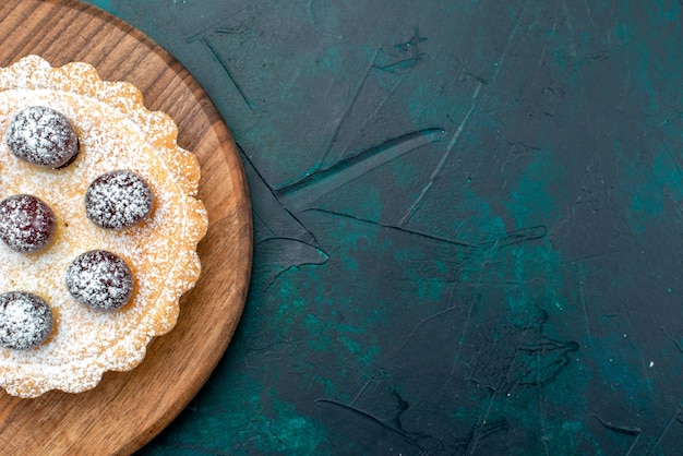 Widok z góry na babeczkę z cukrem pudrem i pysznymi wiśniami na stole