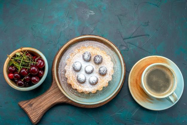 Widok z góry na babeczkę z okrągłymi wiśniami i cukrem pudrem obok talerza wiśni i latte