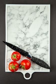 Widok z góry na białą deskę do krojenia z czerwonymi pomidorami na ciemnej powierzchni
