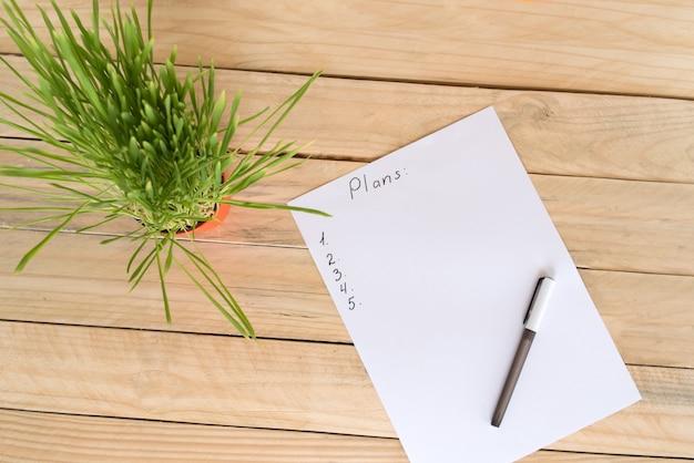 Widok z góry na białą kartkę papieru z planem i piórem, zielona roślina doniczkowa