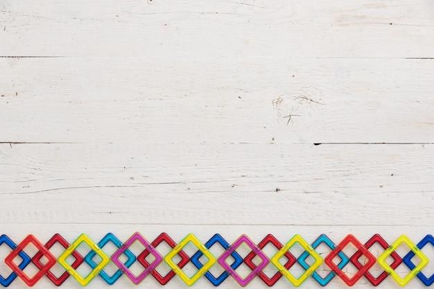 Widok z góry na białe drewniane tło stołu z kolorowymi plastikowymi kształtami i elementami magnetycznymi